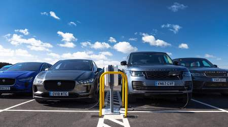 A picture of a newly installed L2 7kW EVSE car charger in Jaguar Land Rover's Gaydan manufacturing site, with Jaguar cars to the left and Land Rover cars to the right.