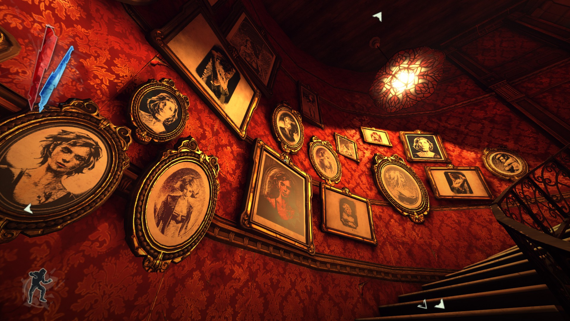 A wall with red wallpaper and filled with portraits.