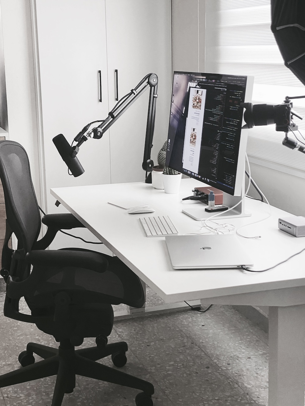 My desk in 2021: a minimalist easthestic including a Macbook, a Pro Display, a sit-to-stand desk, an ergonomic chair, and a professional camera and microphone setup.