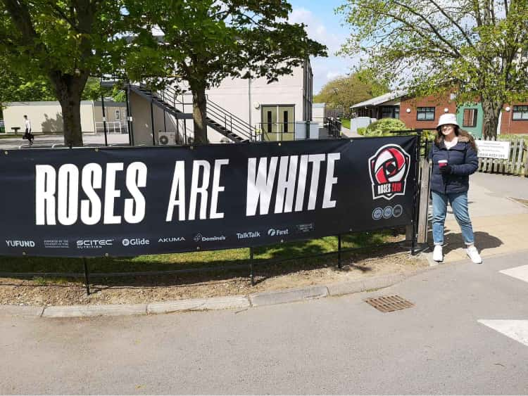 Naomi in her winters coat stood next to a banner that says, Roses are white, on the University of York campus.