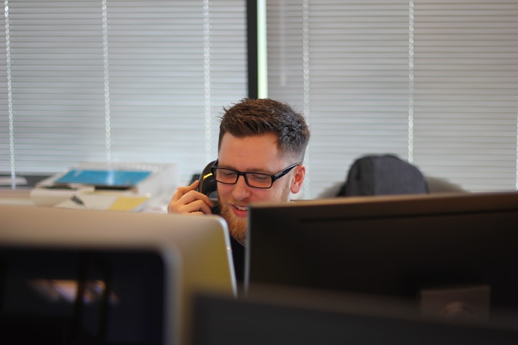 Man talking on office phone and looking at computer screen