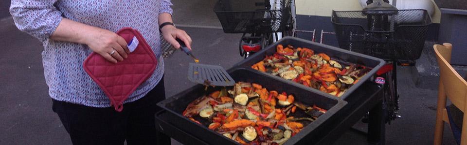 Dörte serviert die Gemüsepfanne für ihre Nachbarn. Gemeinsam essen alle Gäste im kleinen Hinterhof.