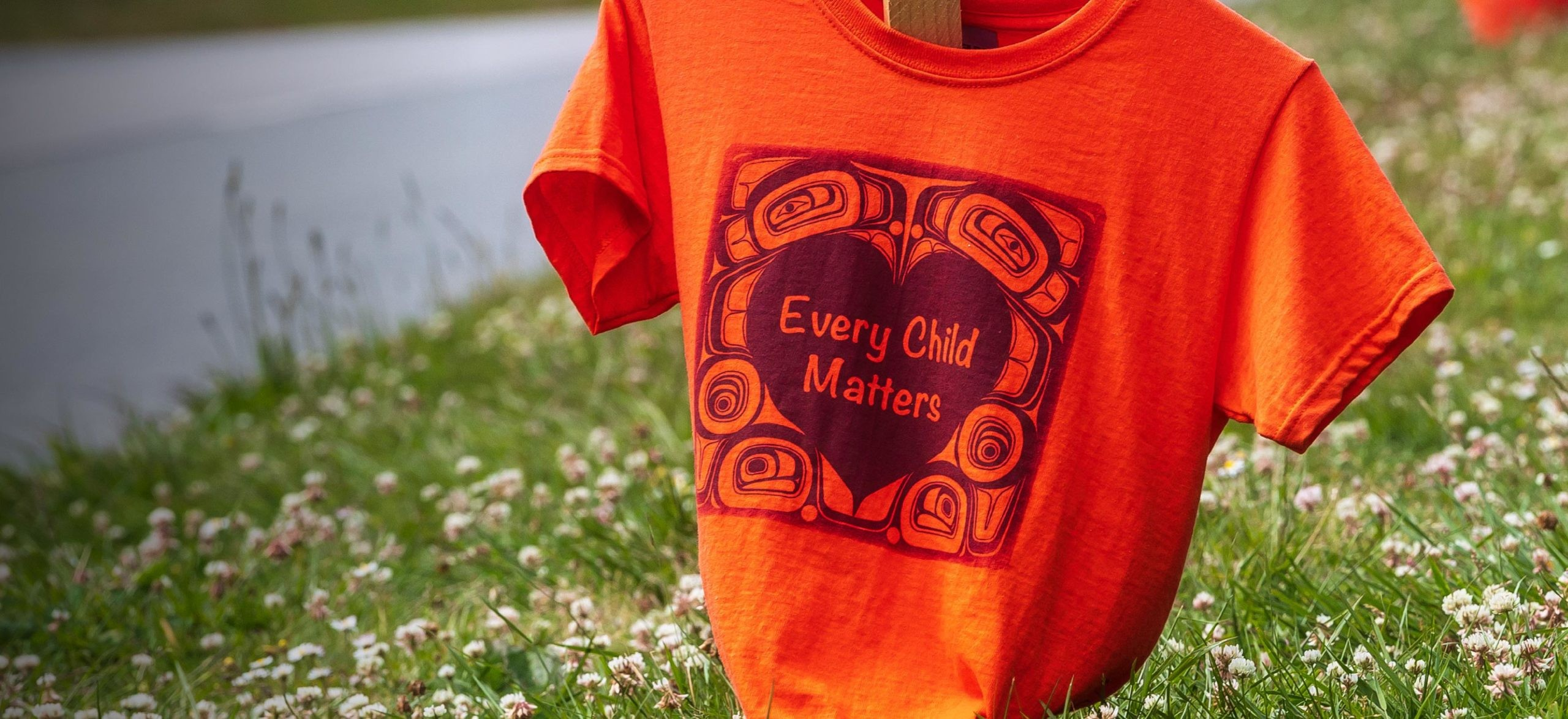 """Orange shirts with the phrase """"Every Child Matters"""" printed on them line Marine Drive in Vancouver as a memorial for the Indigenous children who were sent to residential schools in Canada."""