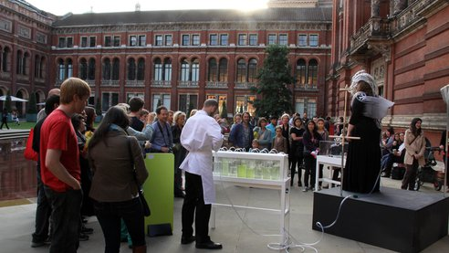 An exterior shot of the V&A museum, where the opera singer performs on stage, flanked by a man in white lab gear poised above a portable set of algae tanks. A crowd listens.