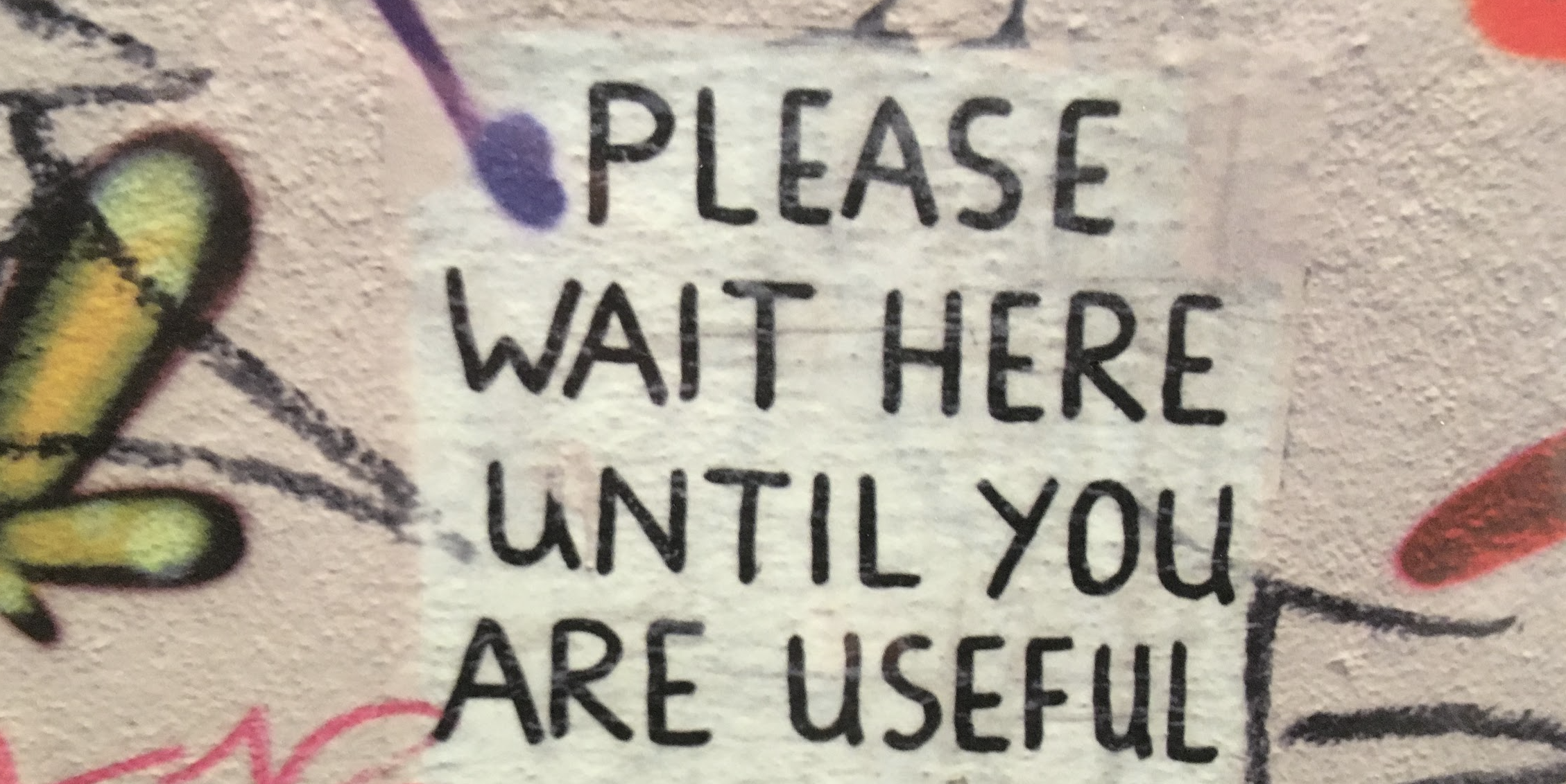 a graffiti saying: please wait until you are useful