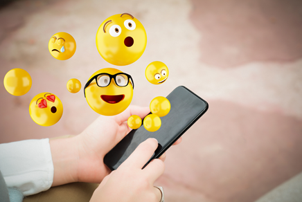 Several emojis floating above mobile phone