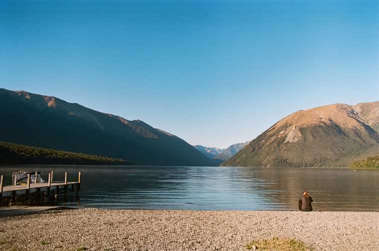 A girl sits, back turned to the camera, on the shore of a glacial lake, looking out into the mountains that frame the lake in the horizon. A dock extends a few meters into the lake on the left.