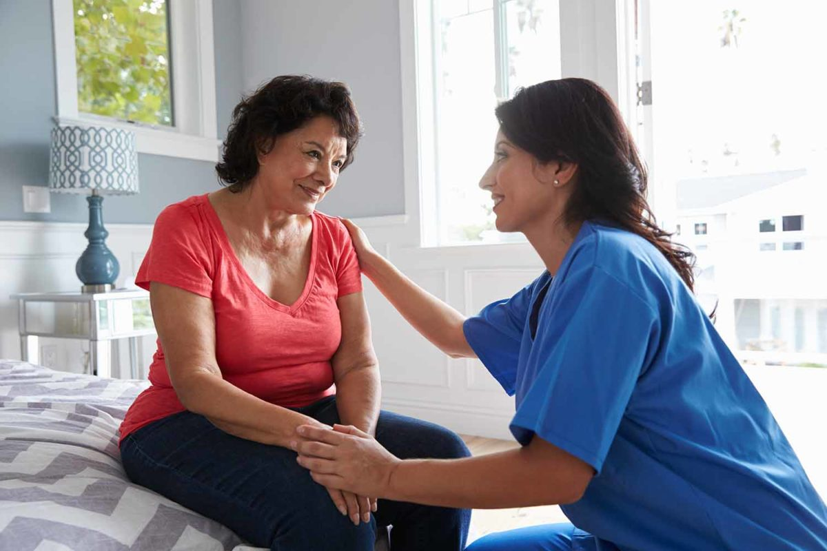 Home care nurse sitting with woman on the edge of a bed