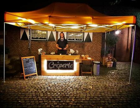 Mobiler Crêpesstand mit natürlicher Holzoptik beim Catering im Außenbereich einer Hochzeitsfeier im Dunkeln mit schöner Beleuchtung