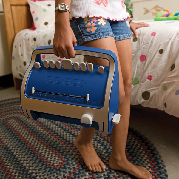 A child carries a new model blue Brailler by a handle, its white plastic keys now numbering 9, and its body encased like a typewriter.