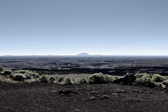 Looking out across the top of a scrub-covered cinder cone across a dark lava field stretching to the horizon. In the center of the frame can be seen an immense lava dome whose base actually lies below the visible horizon.