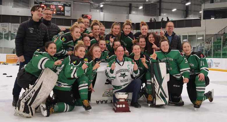 Saskatoon stars women's hockey team on ice wearing hockey equipment in front of a trophy