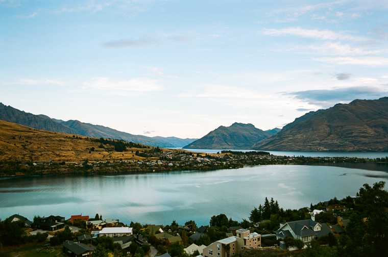 View of Lake Wakatipu surrounded by houses and evergreens with mountains in the distance.