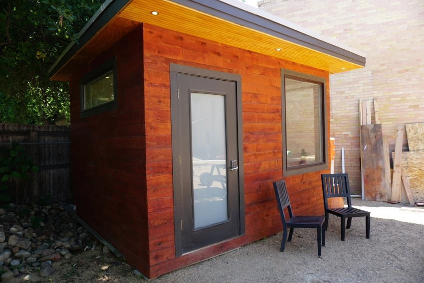 Exterior photo of Mr Money Mustache's 'tiny home', a backyard office with dark red siding and downlights in the soffit.