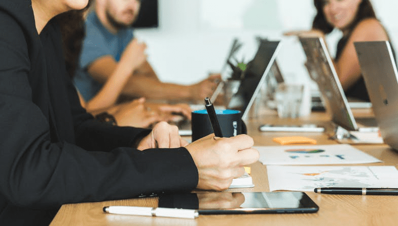 Business colleagues sit across table on laptops, notepads, with phones and pens to discuss cloud forecasting for businesses #business #forecasting
