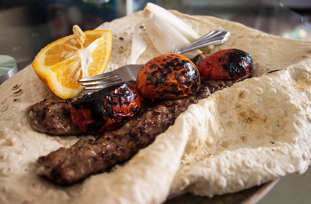 meat kebab on flatbread with roasted tomatoes