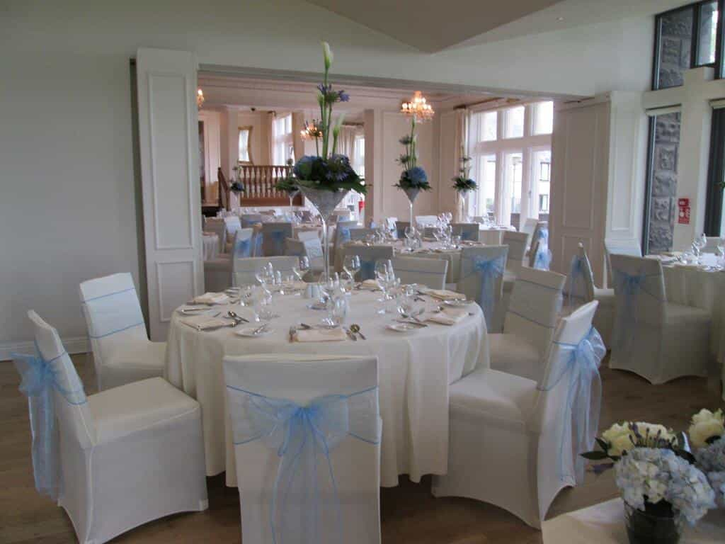 Baby shower meal venue dressing with white table and chair linens and baby-blue decor