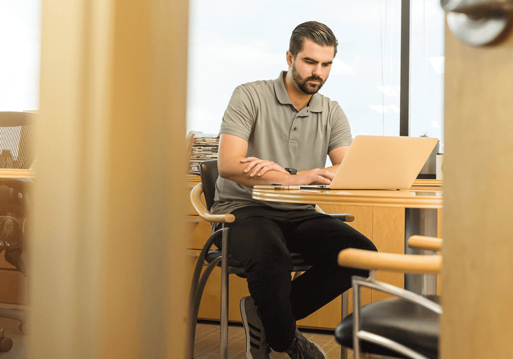 Man working on a laptop representing an Ease employee complying with policies and procedures