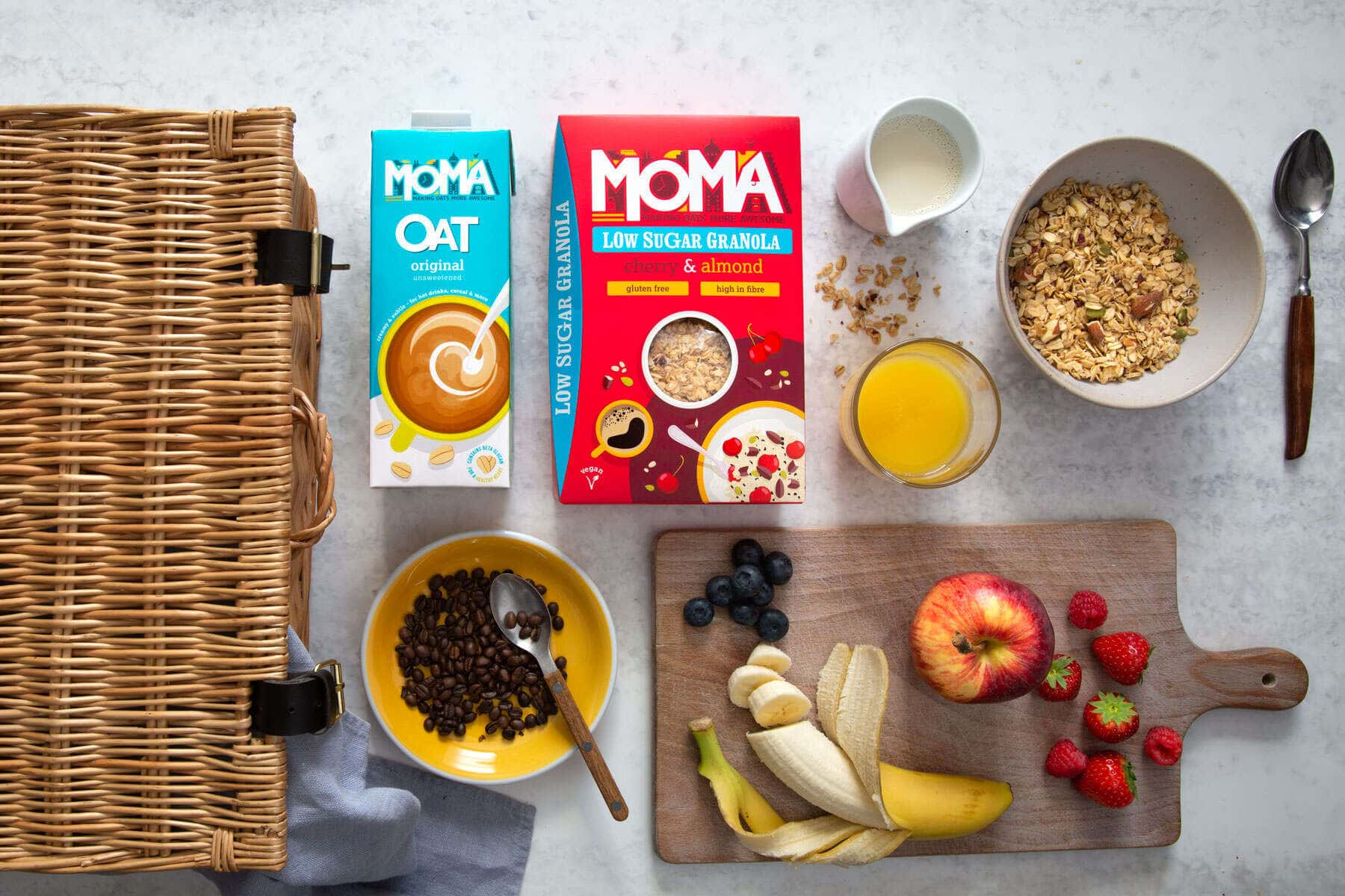 Moma food porridge and Oat milk with an assortment of breakfast condiments next to a picnic hamper