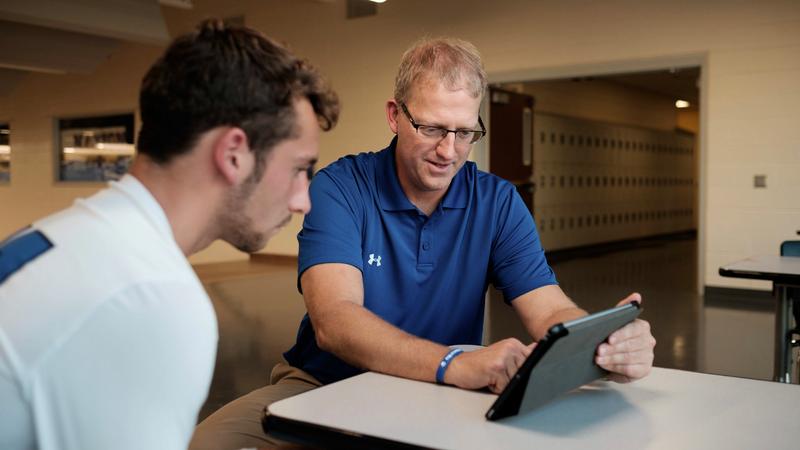 タブレットで選手に分析フィードバックを提供するコーチ