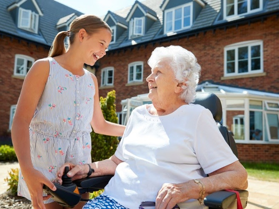 A young girl volunteers at a senior center and talks to an elderly woman outside.