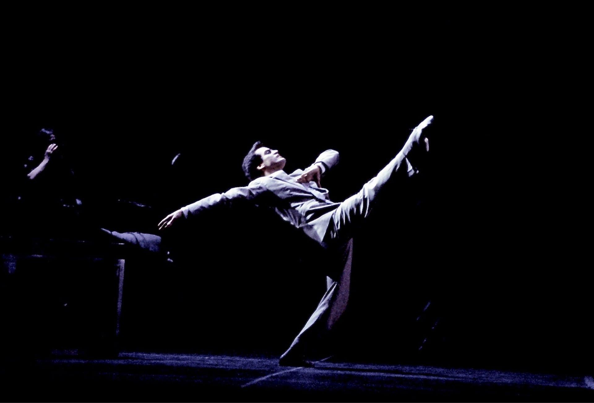Dancer in white suit struts leg extended against dark background.