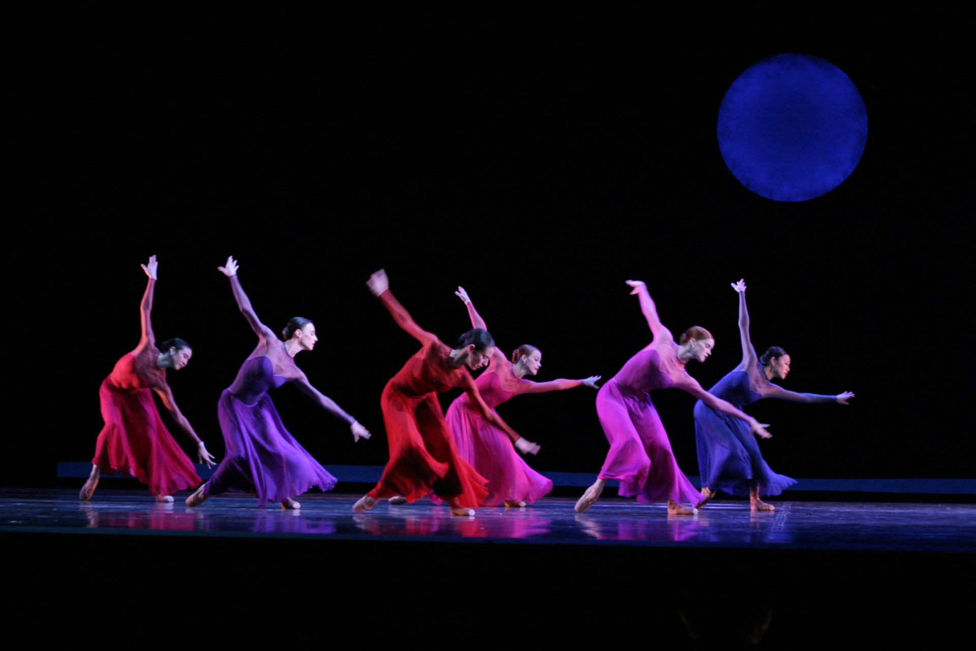 Ballerinas in brightly coloured monochrome dresses dance against blue moon in black sky.