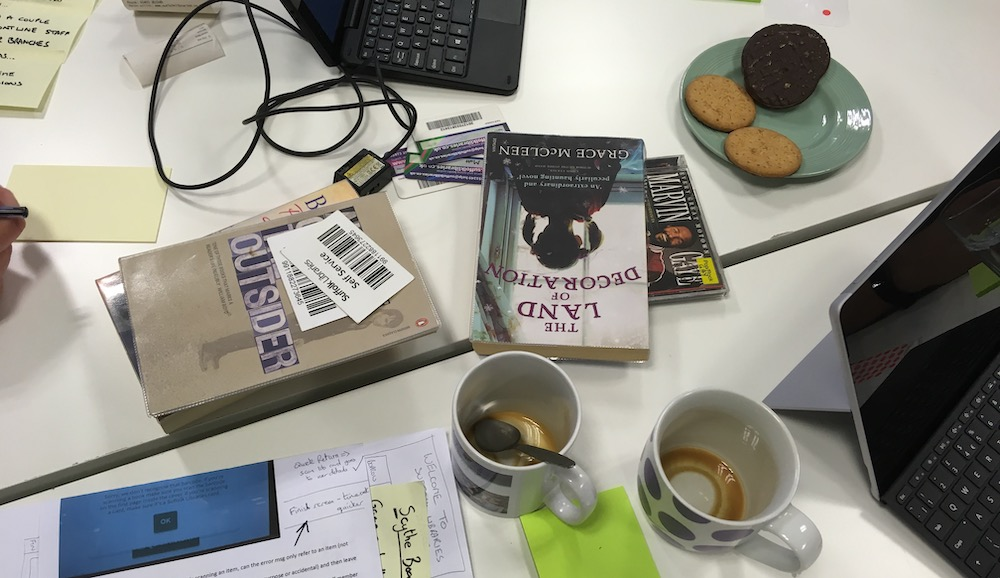 Empty coffee cups, tablets, books and barcode scanners on a table