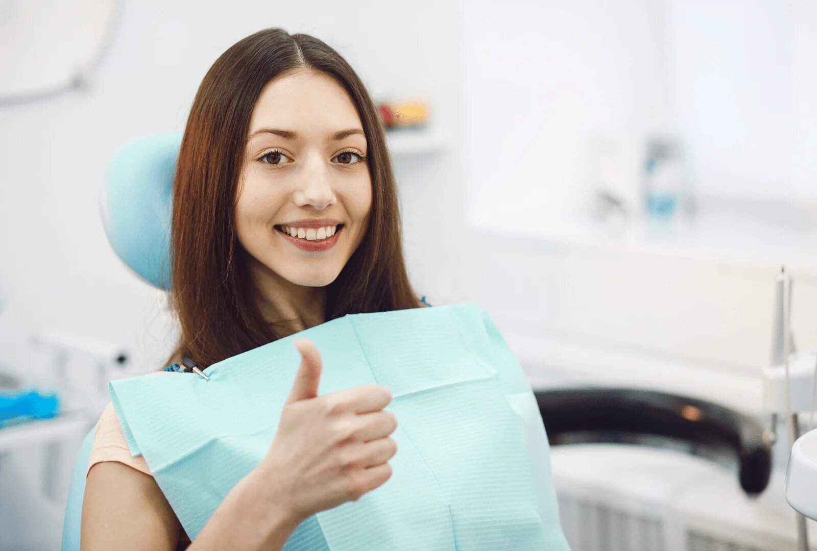 Female patient sitting down smiling at the camera giving a thumbs up signal