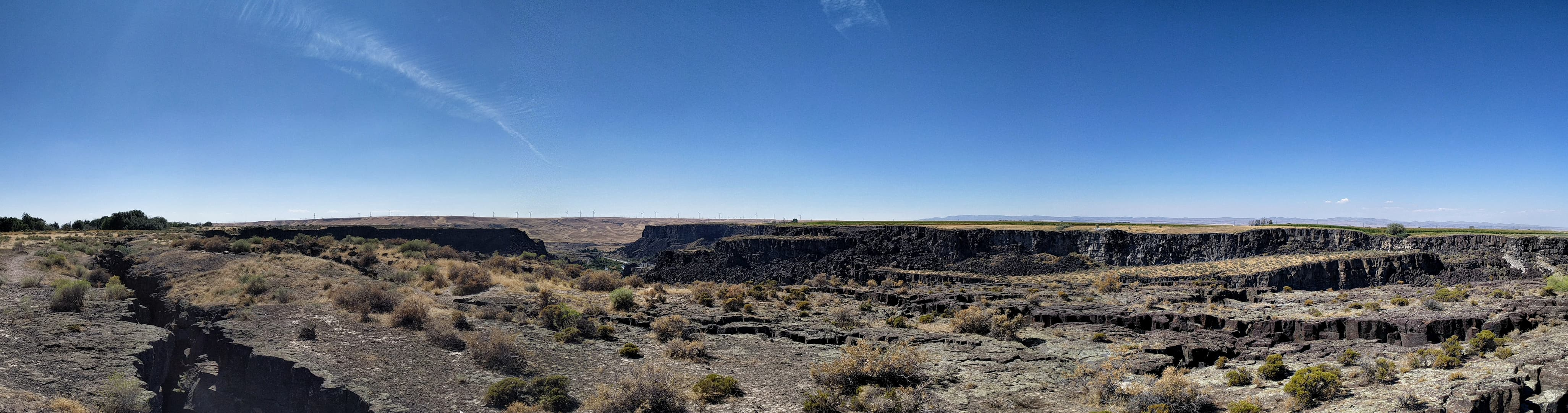 A panoramic view of the Malad River Gorge in Idaho. A wind farm can just be seen in the distance.