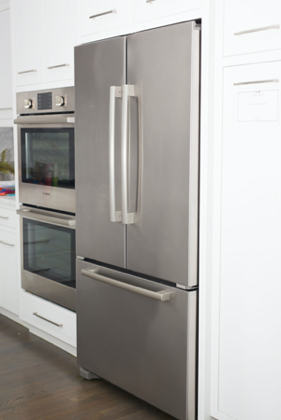 Refrigerator and double oven in kitchen side view