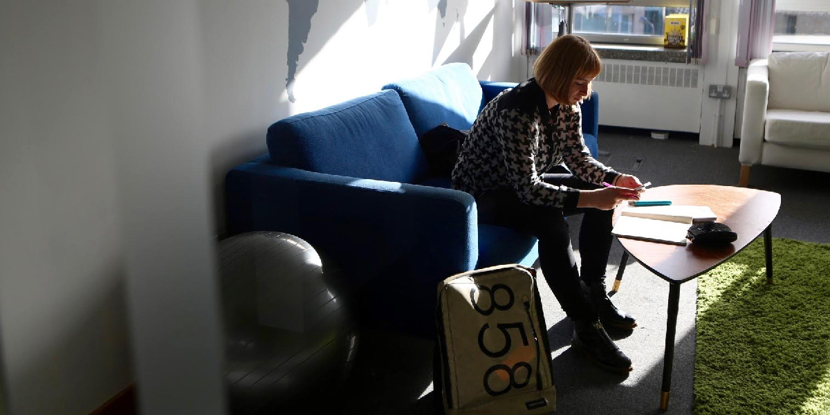 UX designer Alex Humphry-Baker sitting on a sofa, scrolling through her mobile phone