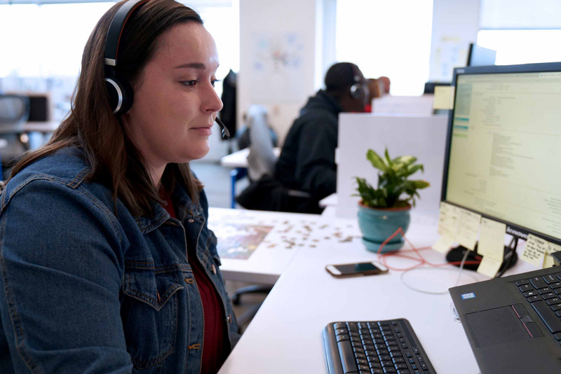 A woman in a denim jacket listens on headphones while sitting at her desk
