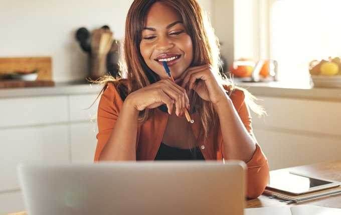 A woman smiles while looking at a computer screen.
