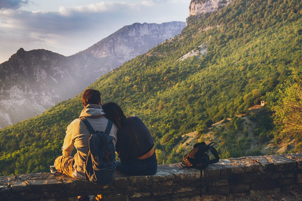 A couple of travelers sitting together in front of a mountain.