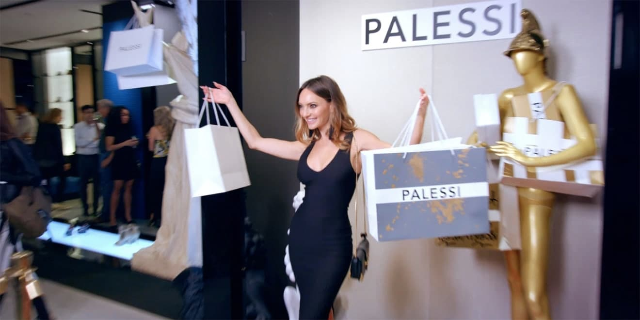 Woman standing outside Palessi store proudly brandishing shopping bags