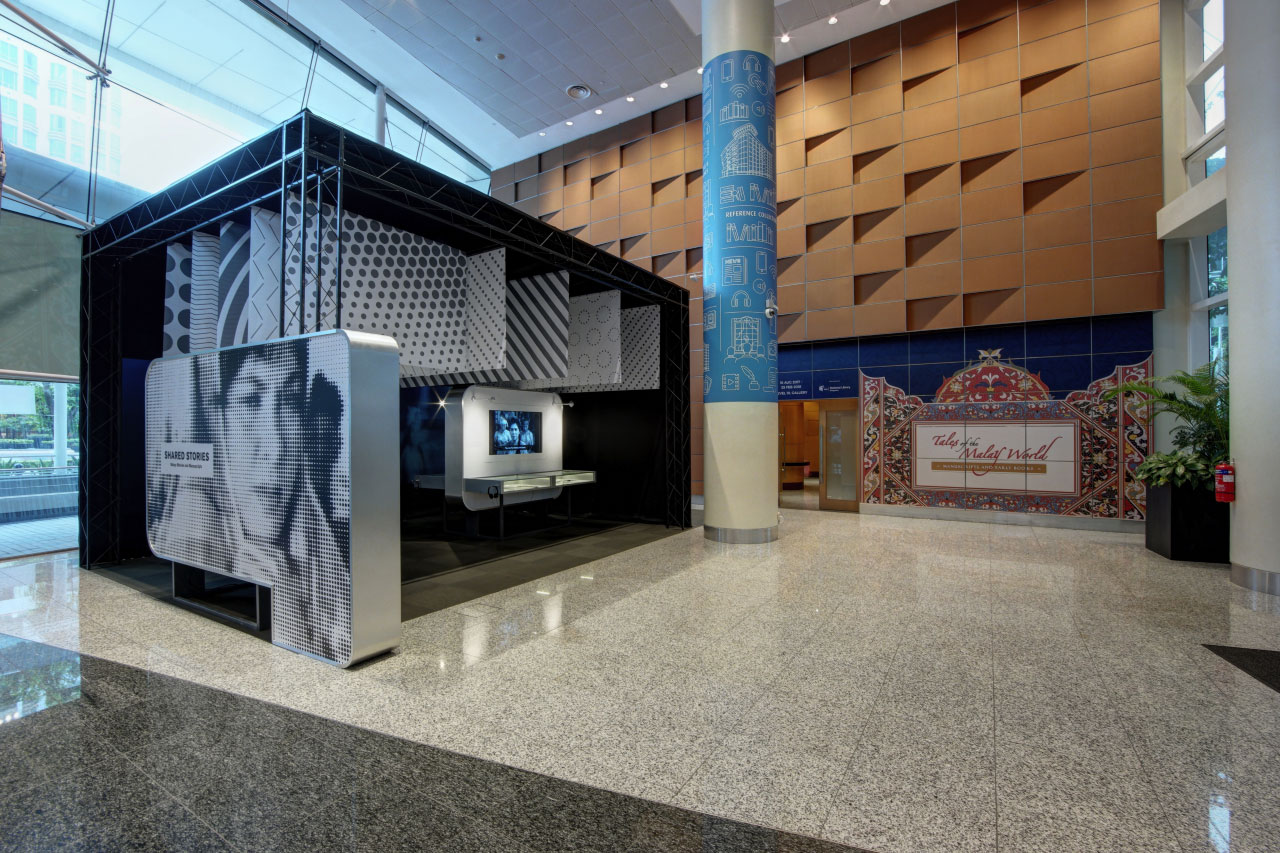 A photo of the Lobby exhibition. A film still of a woman is on the side panel wall. Inside are TV screens showing old movies and there are showcases underneath.