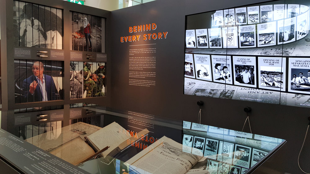 Photo of the News Gallery's 'Behind Every Story' section. It features sliding handles to display different images, along with tall multimedia touchscreens. A showcase featuring physical news articles is in the foreground.