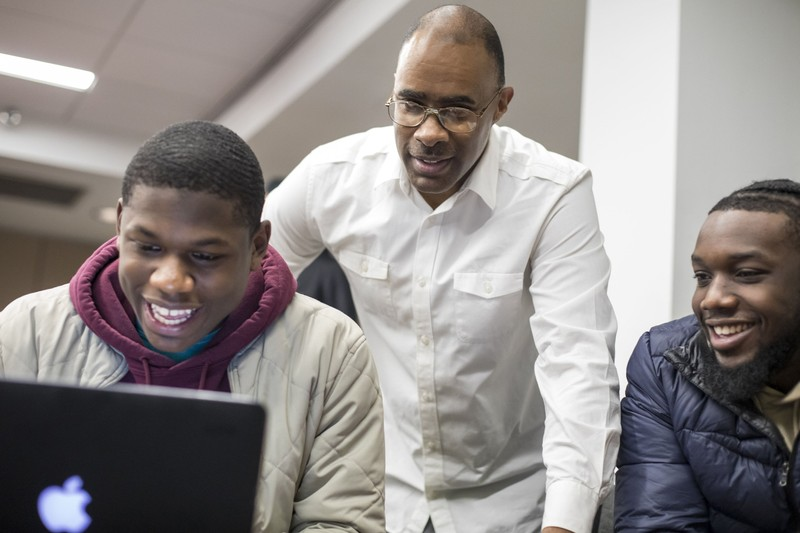 Students and professor working on a computer at Morehouse College