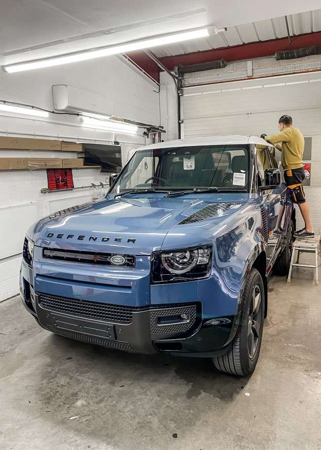White vinyl wrap applied to roof of Blue Land Rover Defender