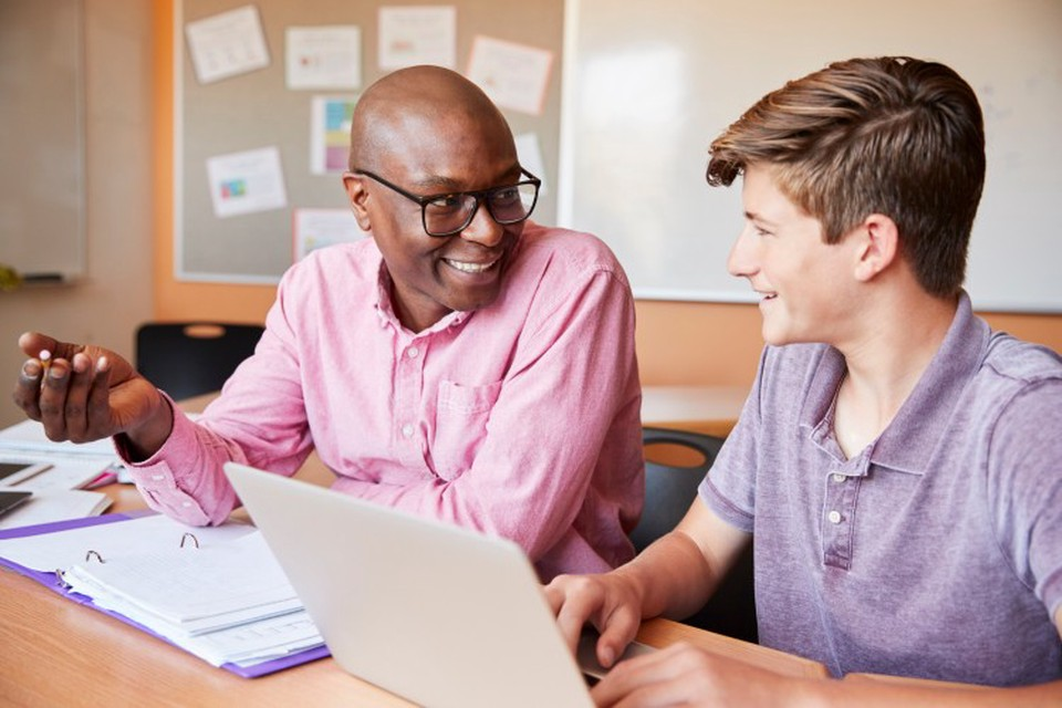 Smiling high school teacher shows good teaching skills working with student at laptop.