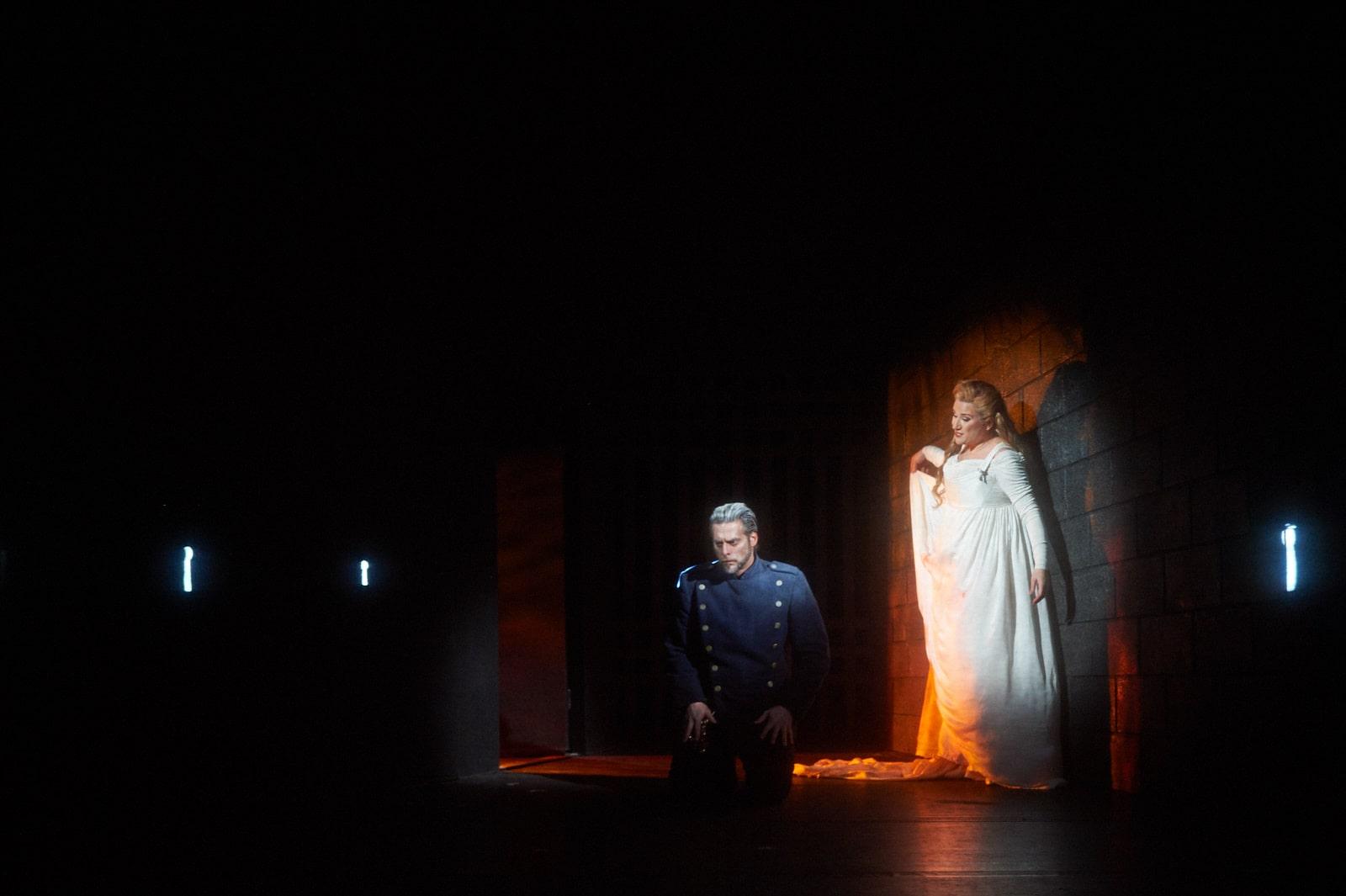 Bride stands spot lit against brick wall with blue uniformed man kneeling beside, keyhole lights piercing the darkness.