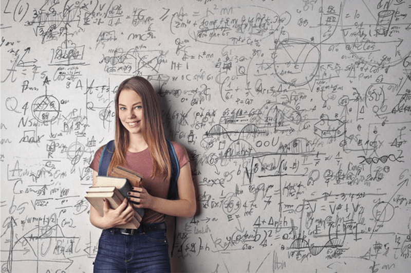 A lady standing in front of a whiteboard with equations written on it.