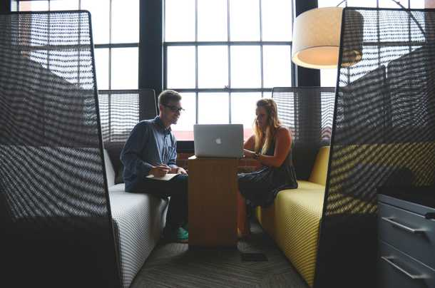 Two people sitting in a booth staring at a laptop