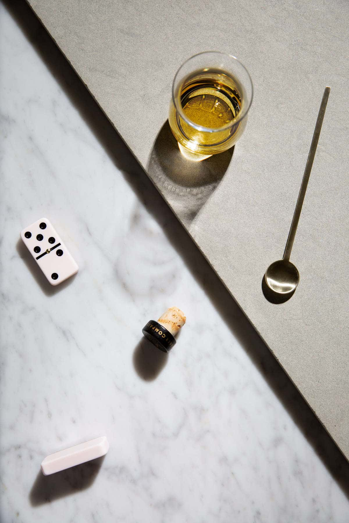 whiskey with dominos next to the glass on marble top