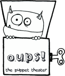 The Oups monster peeking out of a wind up box with Oups! The Puppet Theater written on the box.