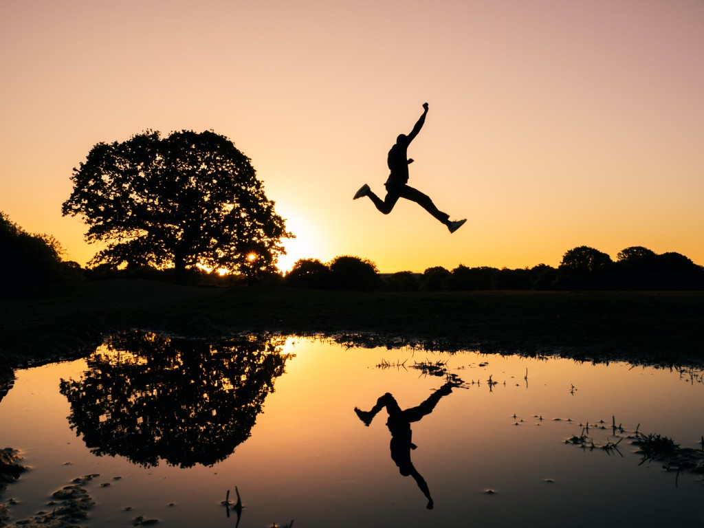 man jumping on body of water during golden hour
