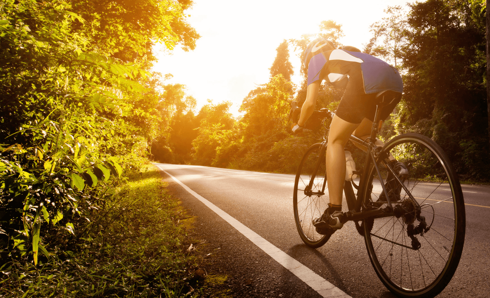 a woman riding a bike along a country road