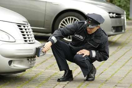 Polizist untersucht Schaden nach Verkehrsunfallflucht.