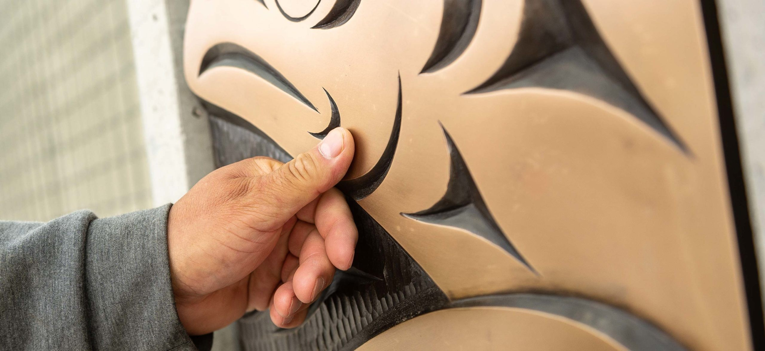 Musqueam artist Brett Sparrow with the bronze cast of his artwork on the UBC Vancouver campus